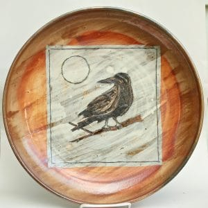 ceramic platter with imagery of a crow and the moon